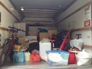 Belongings are packed in the back of a moving truck.