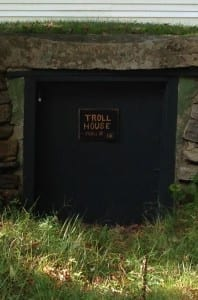 "A short green door has a sign reading ""Troll House. Troll is in."""