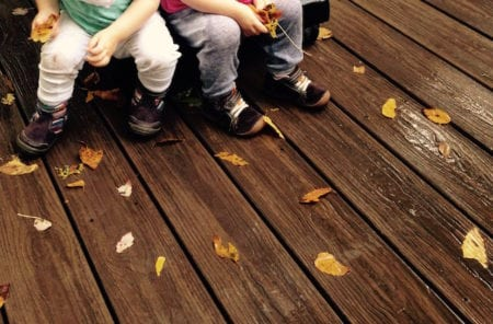 Four toddler feet on a damp deck with leaves